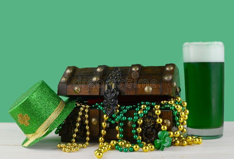 Bild för Sts Patrick dag på mars 17th Skattbröstkorg som symboliserar lycka och rikedom med ett exponeringsglas av grönt öl arkivbild