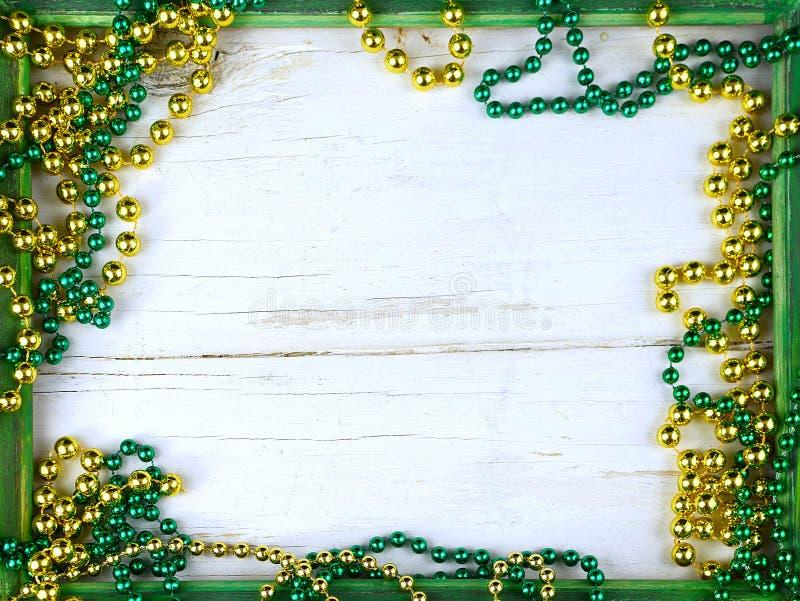 Bild för Sts Patrick dag på mars 17th Skinande gröna och guld- pärlor på en träram med lantligt woden bakgrund royaltyfri foto