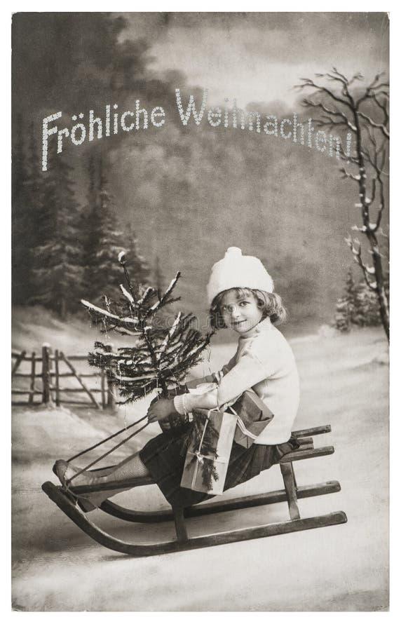 Bild för tappning för liten flickaslädejulgran nostalgisk royaltyfri bild