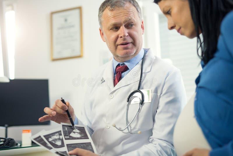 Bild för ultraljud för gynekologdoktorsvisning till gravida kvinnan royaltyfri bild