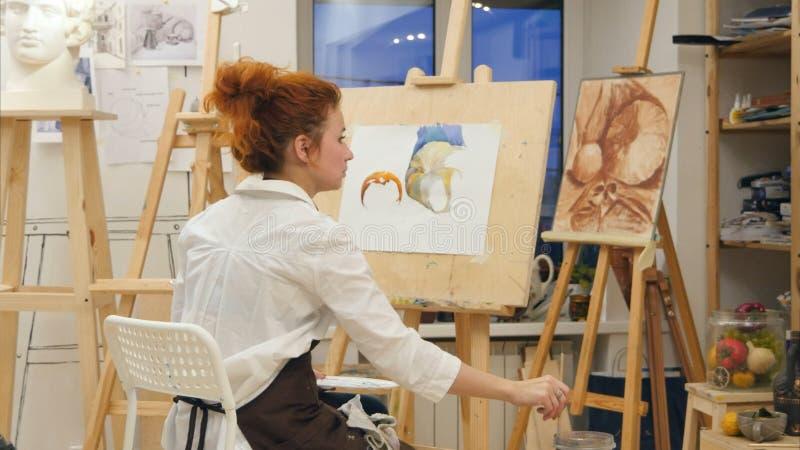 Bild för vattenfärg för kvinnakonstnärmålning i hennes studio royaltyfri bild