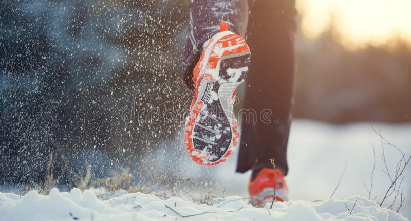 Bild från baksida av den rinnande mannen i gymnastikskor i sportkläder på snö arkivfoton