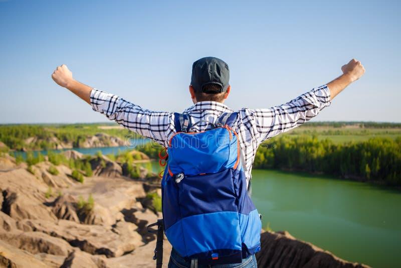 Bild från baksida av den unga turisten med ryggsäcken med händer upp mot bakgrund av berglandskapet, sjö fotografering för bildbyråer