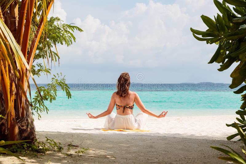 Bild från baksida av en ung kvinna som mediterar på en strand i Maldiverna arkivfoto