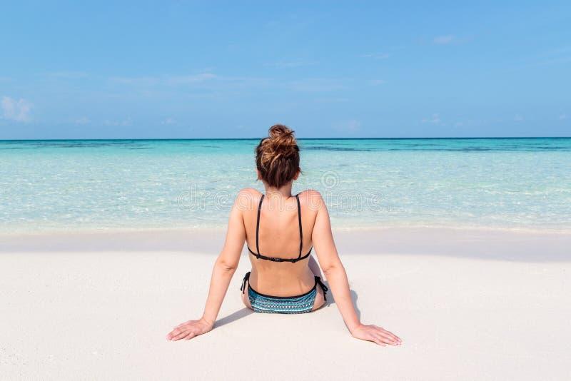 Bild från baksida av en ung kvinna som placeras på en vit strand i Maldiverna Kristallklart bl?tt vatten som bakgrund royaltyfri fotografi