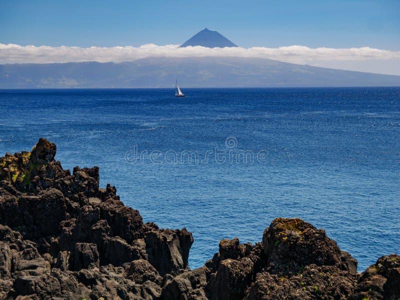 Bild från en klippa med en segelbåt i det atlantiskt och ön av Pico med berget Pico i bakgrunden royaltyfri fotografi