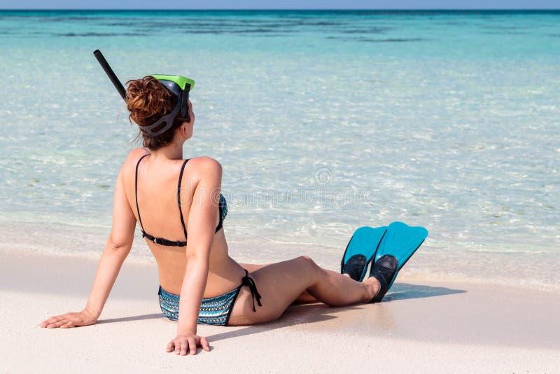 Bild fr?n baksida av en ung kvinna med flipper och maskeringen som placeras p? en vit strand i Maldiverna Kristallklart bl?tt vat royaltyfria foton