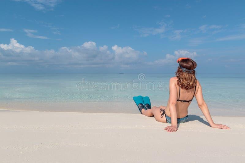 Bild fr?n baksida av en ung kvinna med flipper och maskeringen som placeras p? en vit strand i Maldiverna Kristallklart bl?tt vat royaltyfri fotografi