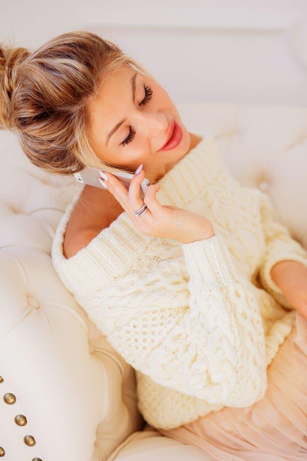 Bild hübscher Dame sitzend im Büro auf Stuhl Unter Verwendung des Laptops Unterhaltung durch Handy lizenzfreies stockbild