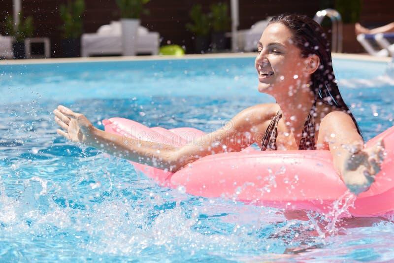 Bild im Freien der entspannten spielerischen Frau, die Spaß im Swimmingpool allein, liegend auf rosa Wassermatratze, Spritzwasser stockbild