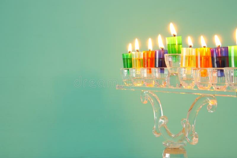 Bild jüdischen Feiertag Chanukka-Hintergrundes mit Kristall-menorah u. x28; traditionelles candelabra& x29; und bunte Ölkerzen stockfotografie