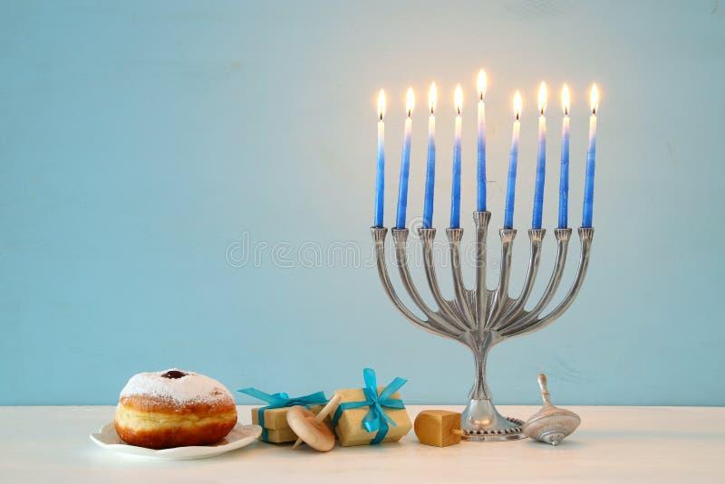 Bild jüdischen Feiertag Chanukka-Hintergrundes mit traditioneller spinnig Spitze, menorah u. x28; traditionelles candelabra& x29; lizenzfreies stockbild