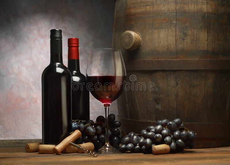 Bild med vinflaskor, vinglaset av rött vin, den trägamla trumman och den mörka druvan royaltyfri bild