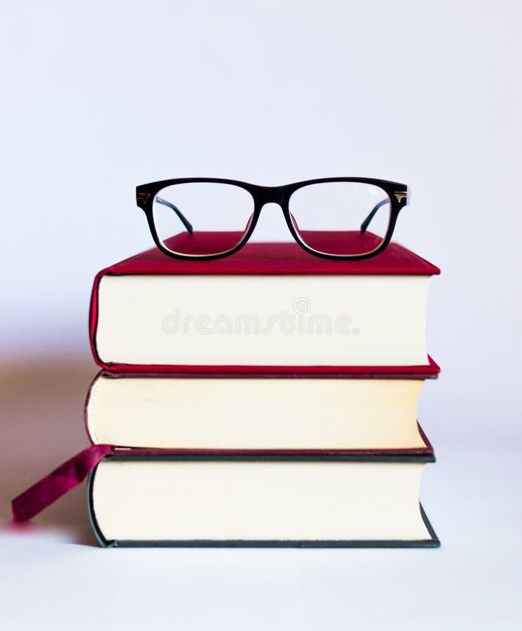 Bild mit Büchern und Gläsern auf weißem Hintergrund stockfotografie