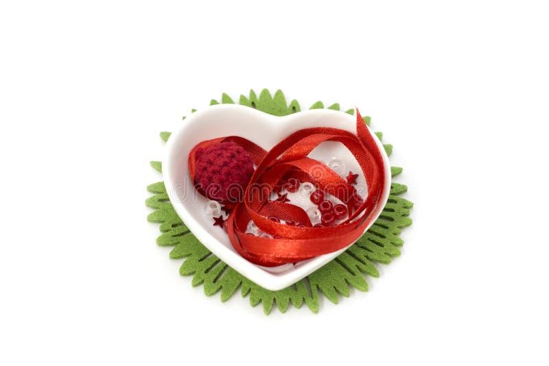 Bild mit rotem Band, kleiner Schüssel der Herzform und Dekorationen lizenzfreie stockfotos