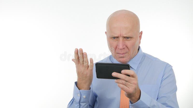 Bild mit schlechten Nachrichten verärgerter Geschäftsmann-Reading Astonished Financials auf Mobiltelefon stockfotografie