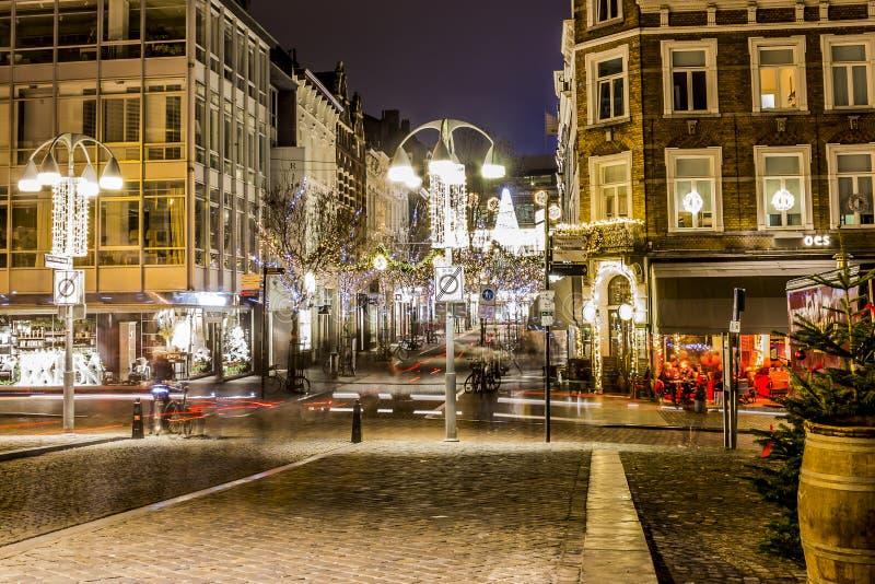 Bild på natten av en tyst december gata med garnering för julljus arkivbild