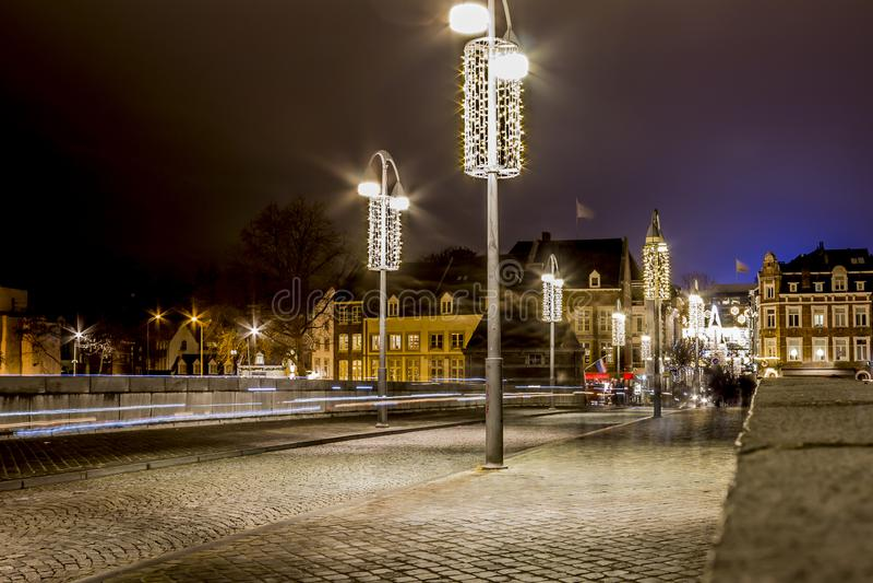 Bild på natten av tysta december på bron Sint Servaasbrug med garnering för julljus arkivfoton