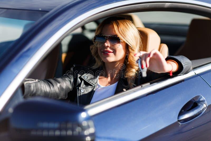 Bild på sida av den unga blonda kvinnan med tangenter som sitter i bil royaltyfri foto