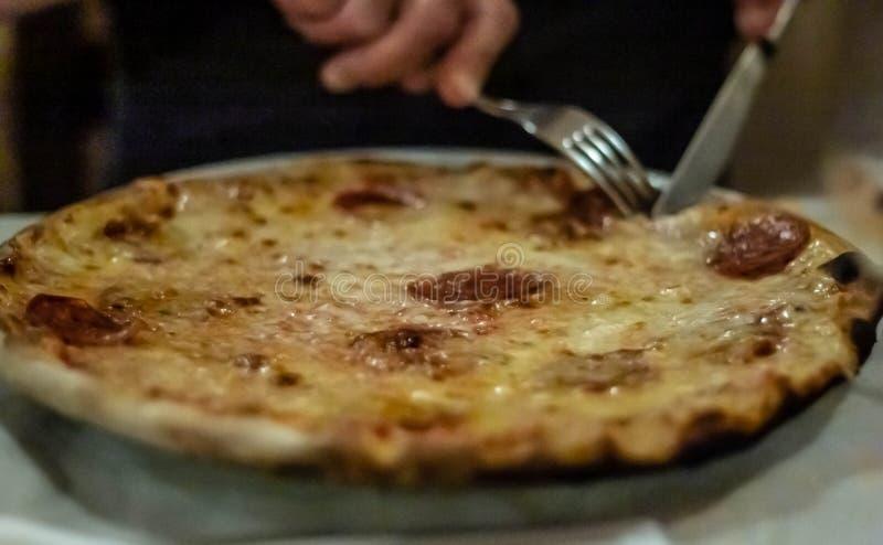 Bild som beskriver en härlig och läcker pizza, medan den ska just att skivas och ätas royaltyfri bild