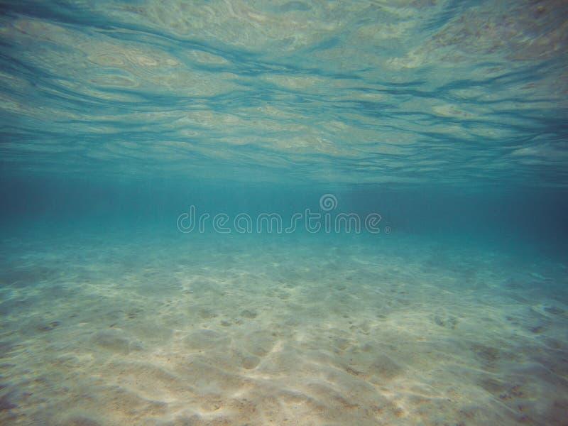 Bild taget undervattens- Klart blått vatten och vit sand royaltyfri bild