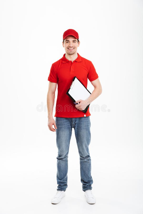 Bild in voller Länge des jungen Kuriermannes 20s in der roten Uniform und im je lizenzfreie stockfotografie
