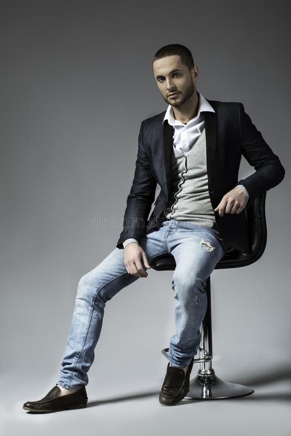 Bild in voller Länge eines jungen Geschäftsmannes, der auf einem Stuhl sitzt stockfoto