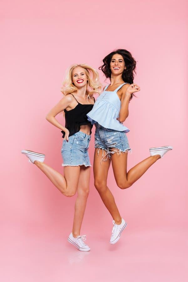 Bild in voller Länge von zwei glücklichen Frauen im Sommer kleidet stockbilder