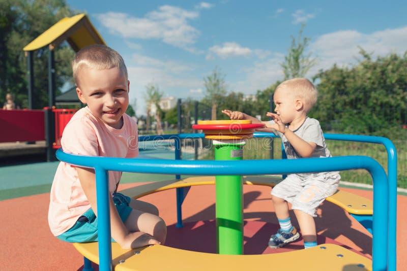 Bild von den frohen Geschwister, die Spaß auf Karussell draußen haben stockfotografie
