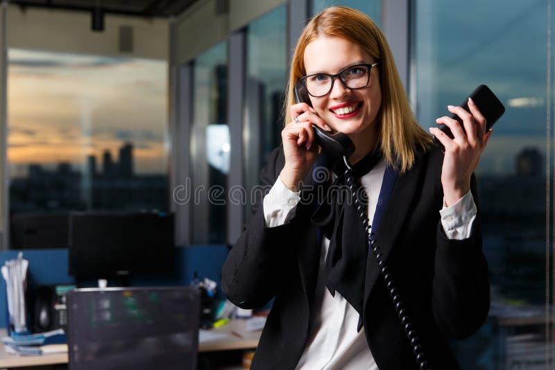 Bild von den lächelnden tragenden Gläsern der Frau, die am Telefon sprechen lizenzfreies stockbild