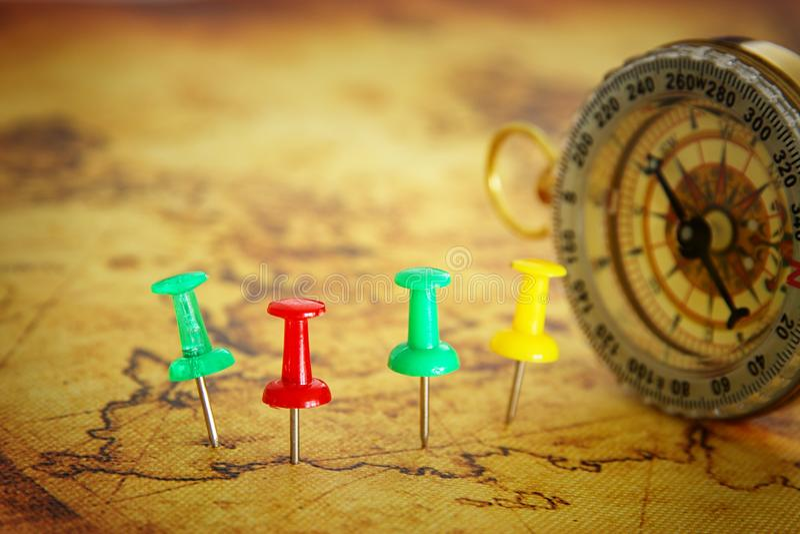 Bild von den Stiften befestigt zur Karte, Standort oder Reiseziel über alter Karte nahe bei Weinlesekompaß zeigend Selektiver Fok lizenzfreies stockbild