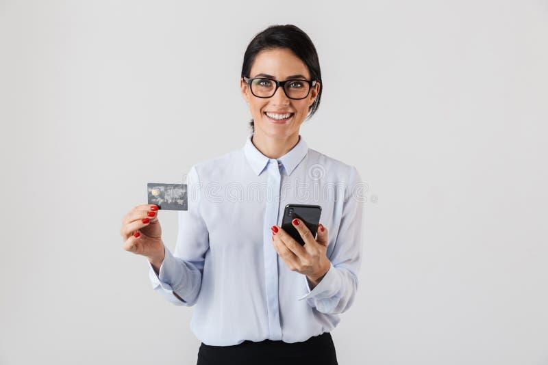 Bild von den tragenden Brillen der intelligenten Bürofrau, die Handy und Kreditkarte, lokalisiert über weißem Hintergrund halten stockbilder