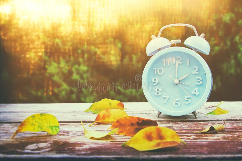 Bild von Herbst Zeitumstellung Zurück fallen Konzept Trocknen Sie Blätter und Weinlesewecker lizenzfreie stockfotos
