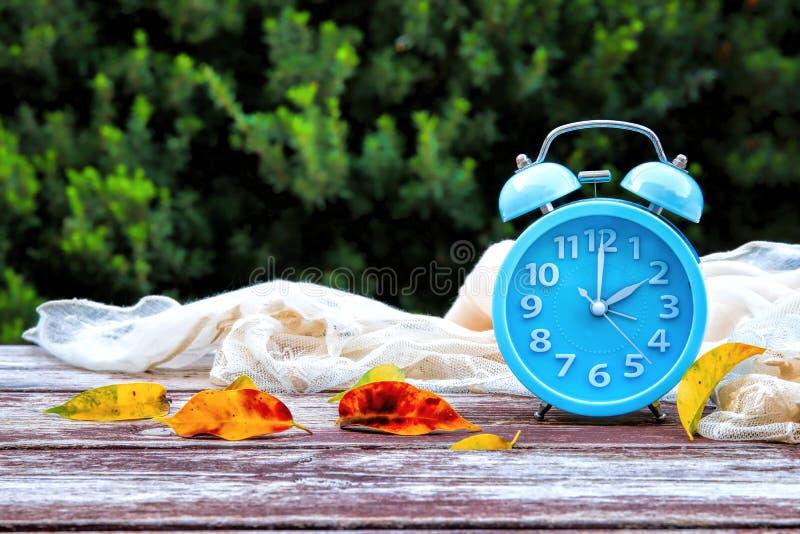 Bild von Herbst Zeitumstellung Zurück fallen Konzept Trocknen Sie Blätter und Weinlesewecker auf Holztisch stockbild