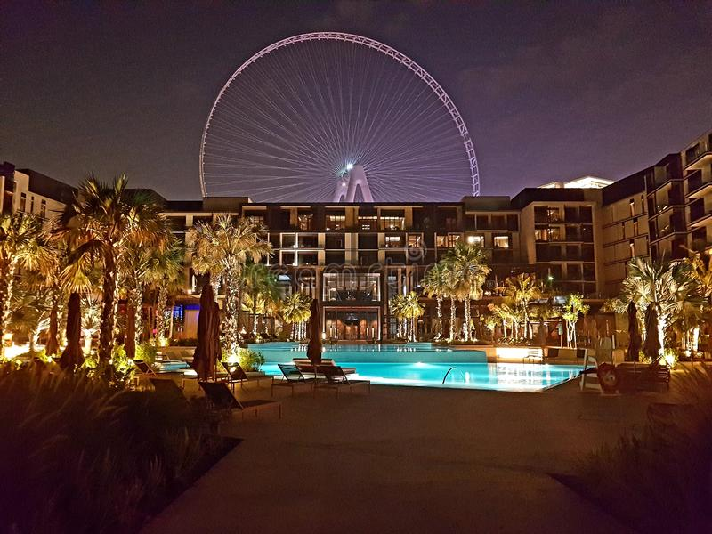 Bild von Hotel Dubais Caesar Palace von der Poolseite mit BluewatersRiesenrad herein Hintergrund Hotelentwurfshintergrund lizenzfreie stockfotografie