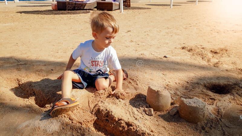 Bild von 3 Jahren alten kleinen Kleinkindjungen, die auf dem Seestrand und dem errichtenden Schloss vom nass Sand sitzen stockbild