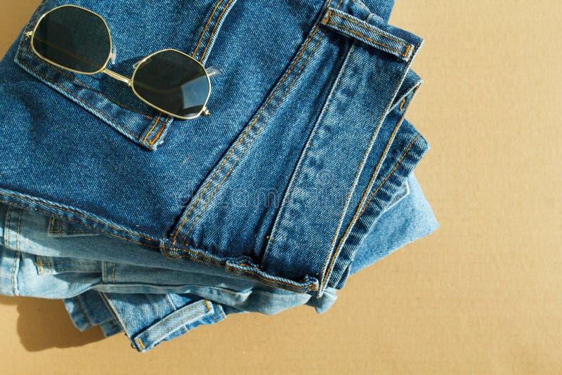 Bild von Jeans mit Gläsern auf hölzernem Hintergrund des Handwerks stockbilder