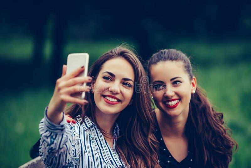 Bild von jungen erstaunlichen Freundinnen, die Studenten, die im Park sitzen, machen selfie durch Handy lizenzfreies stockfoto