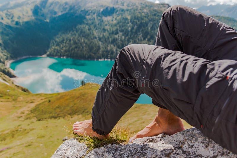 Bild von m?nnlichen F??en und von Beinen mit Bergen und von See von Ritom als Hintergrund lizenzfreie stockfotografie