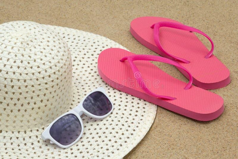 Bild von rosa Flipflops, Sonnenbrille und Hut auf Strandsand stockfotografie