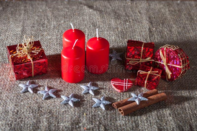 Bild von Weihnachtsdekorationen, Kerzen, Geschenke auf Leinenhintergrund lizenzfreies stockbild