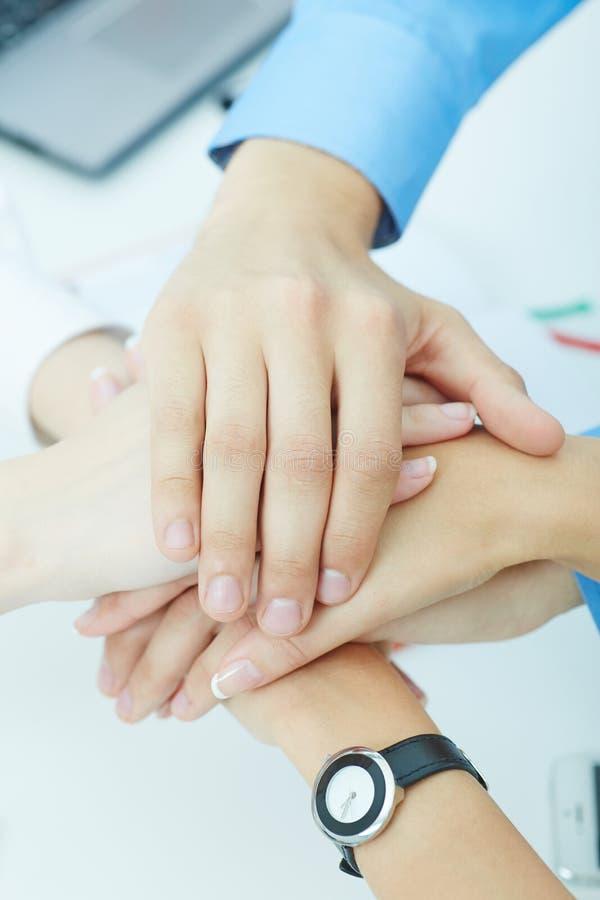 Bild von Wirtschaftlerhänden auf einander als Symbol ihrer Partnerschaft stockfotografie