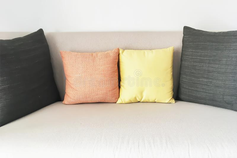 Bild von zwei gelb und von orange kleinen Kissen zwischen zwei schwarzen großen Kissen stockfotografie