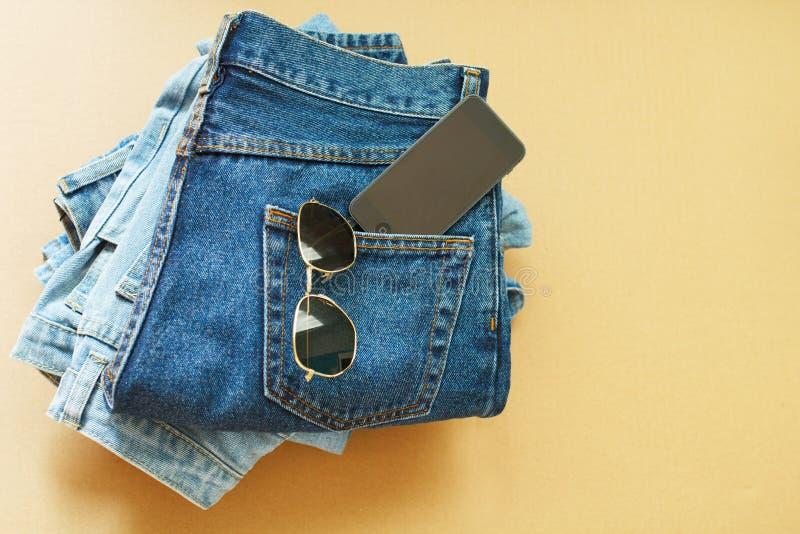 Bild von zwei Jeans mit Mobile in der Tasche und in den Gläsern stockfotografie