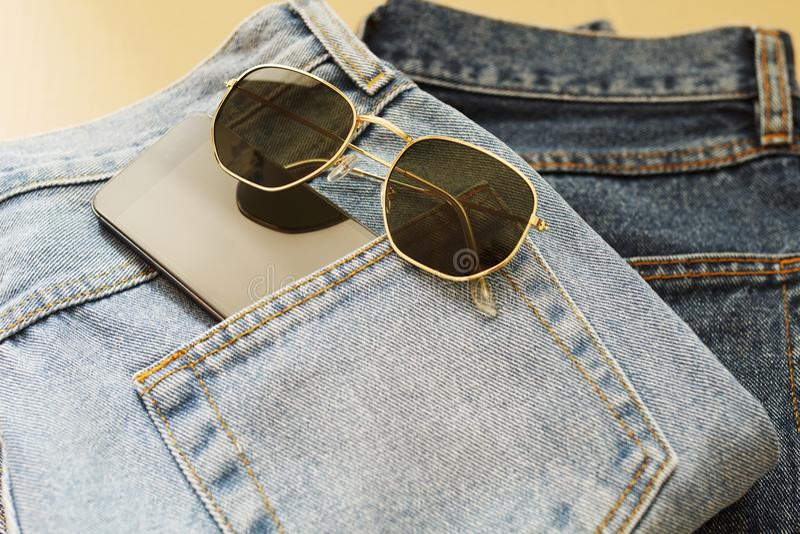 Bild von zwei Jeans mit Mobile in der Tasche und in den Gläsern stockbild