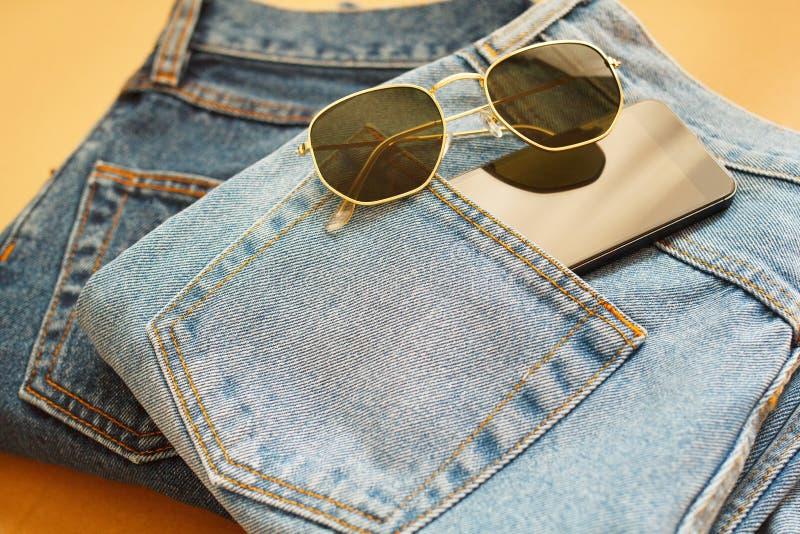 Bild von zwei Jeans mit Mobile in der Tasche und in den Gläsern auf Handwerk stockfoto