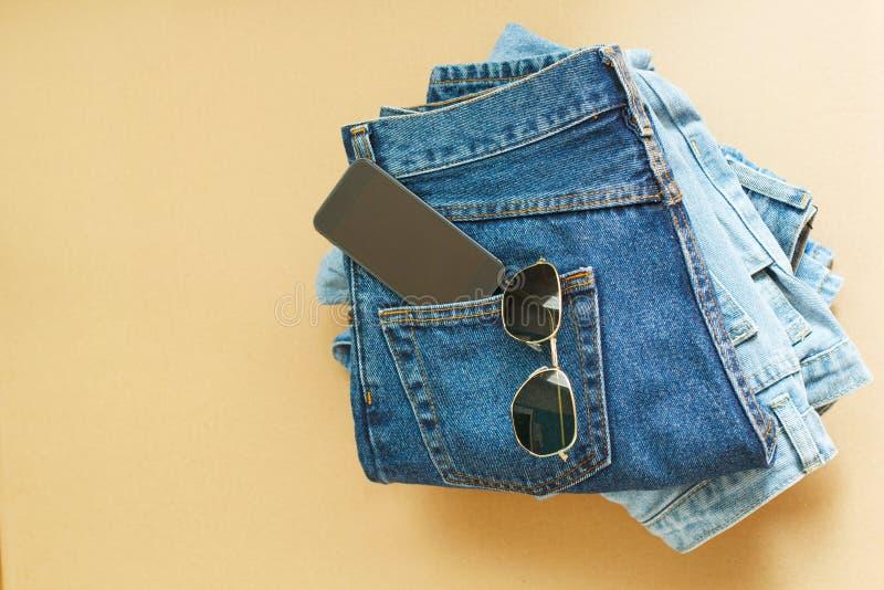Bild von zwei Jeans mit Mobile in der Tasche und in den Gläsern auf Handwerk lizenzfreie stockfotografie