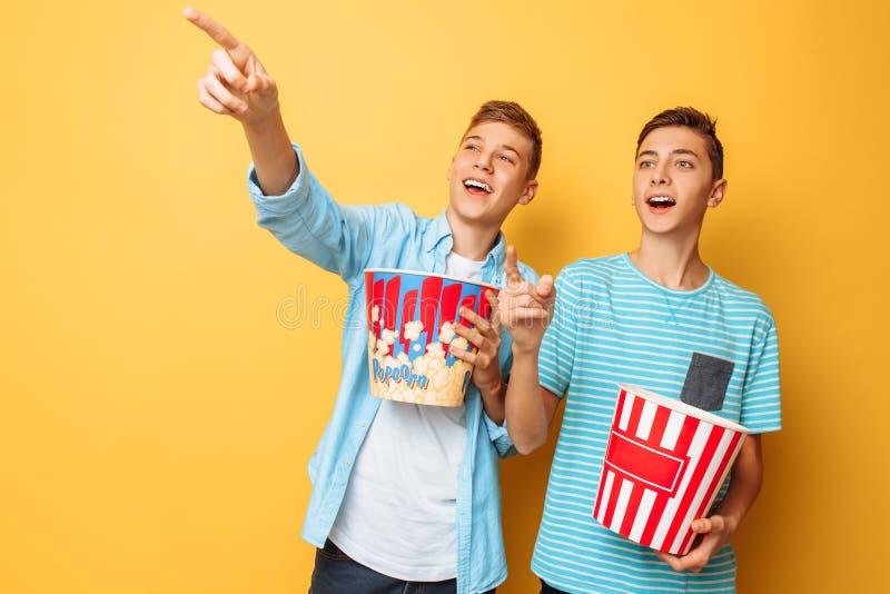 Bild von zwei regte schöne Jugendliche, die Kerle auf, die einen interessanten Film aufpassen und Popcorn auf einem gelben Hinter lizenzfreies stockfoto