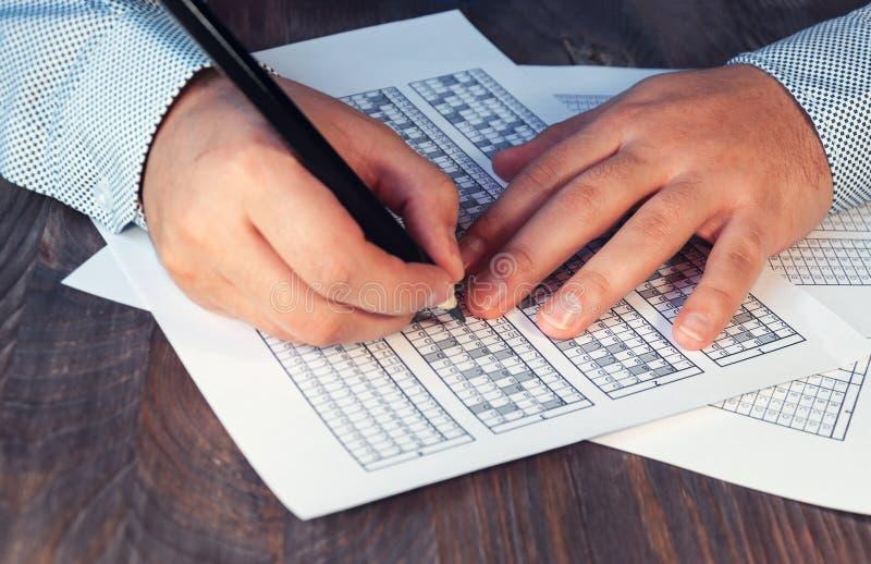 Bilda för examen för mannen på tabellen Provning för utbildning och att hyra Högerhänt och vänsterhänt Selektivt fokusera ton arkivbilder