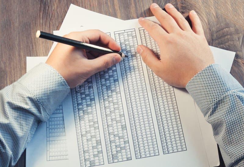 Bilda för examen för mannen på tabellen Provning för utbildning och att hyra Högerhänt och vänsterhänt Selektivt fokusera ton arkivbild
